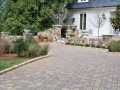 paver driveway with cobble edging and fieldstone walls and columns
