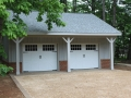 2 car garage with board and batten siding, carriage doors, brick foundation, and paver apron